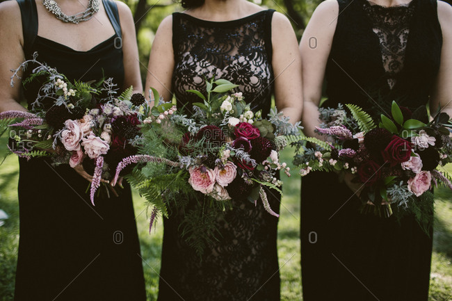 Three bridesmaids in black dresses holding bouquets
