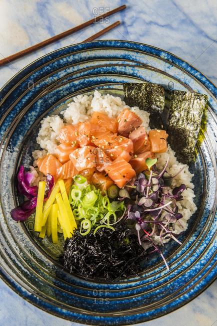 Salmon poke with pickled vegetables, hijiki, microgreens and seaweed