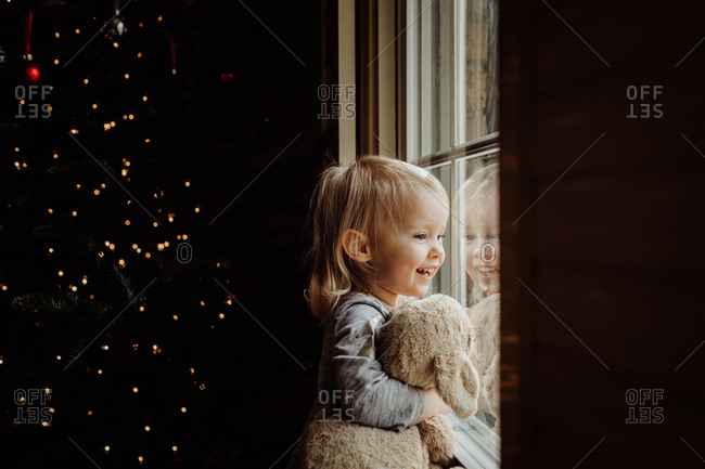 Little girl looking out the window holding her stuffed animal