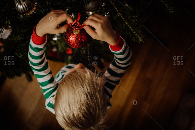 Little boy hanging an ornament on the Christmas tree