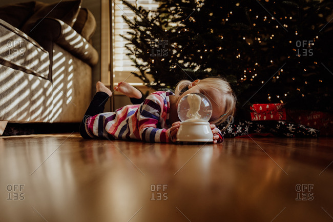Little girl looking at snow globe