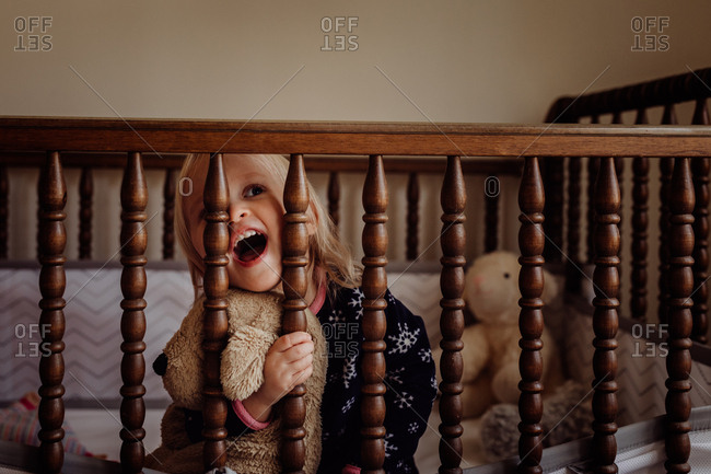Little girl playing in crib