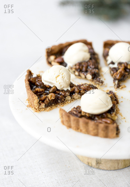 Caramel Nut Tart slices, each topped off with a scoop of ice cream