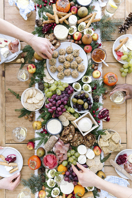 A savory selection board for friends, with cheese, grapes, olives, breads, ham, eggs and fruit