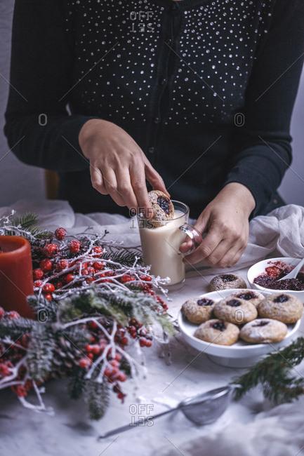 Woman eating spelt thumbprint cherry jam cookies