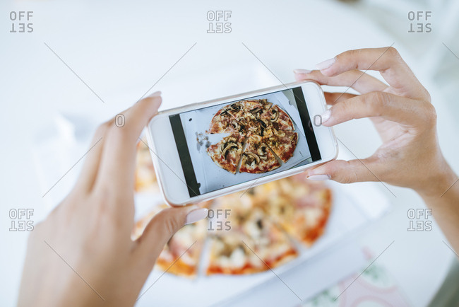 Woman taking a picture of a pizza with a smartphone