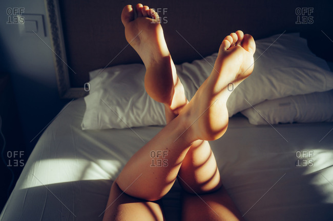 Woman's legs in bed with blind shadows