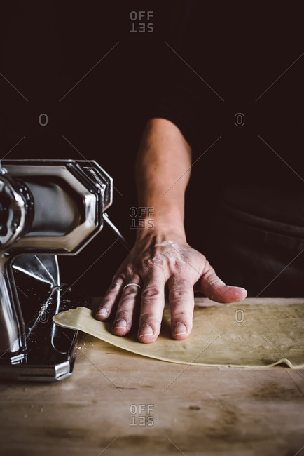 Person preparing a sheet of homemade pasta dough
