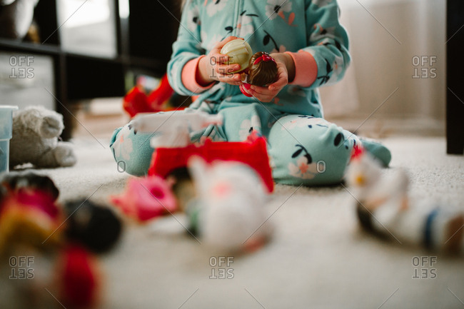 Child wearing pajamas sitting on floor playing with toys
