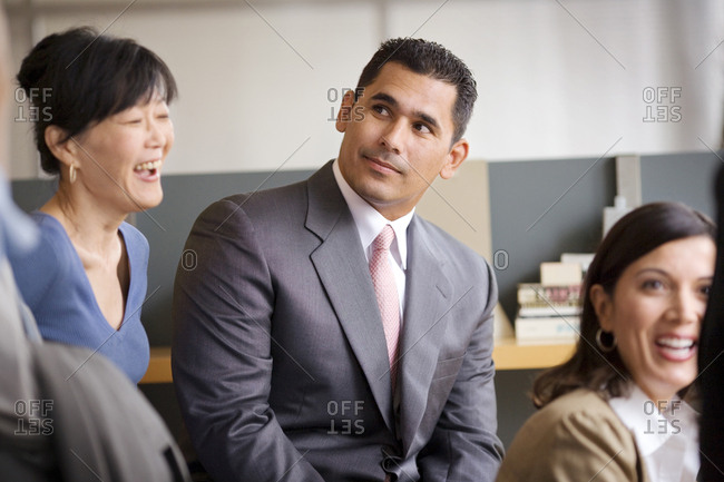 Mid-adult businessman sitting in an office next to two female work colleagues