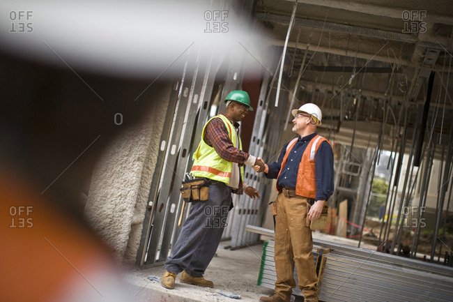 Mature male construction worker shaking hands with a mid-adult co-worker on a building site