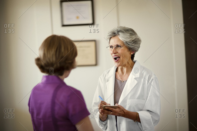 Friendly mature female doctor smiles as she chats to a patient