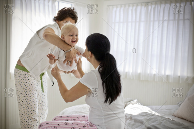 Toddler being held up by a mid-adult woman while another looks on