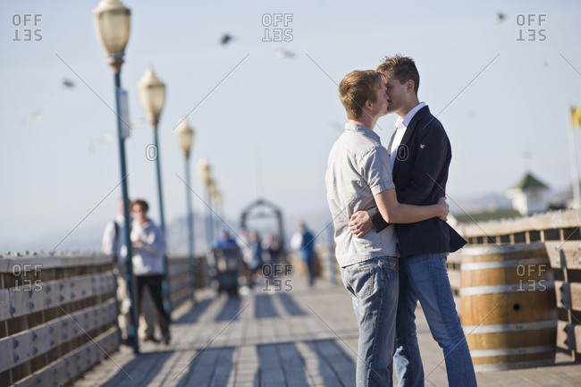 Young homosexual male couple kissing on a pier
