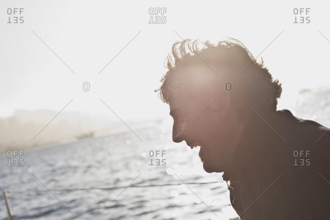 Mid-adult man sitting on a sail boat at sea