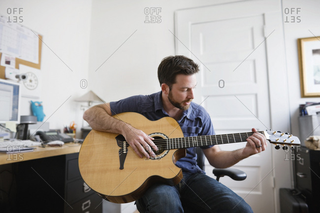 Young adult man playing an acoustic guitar in a home office