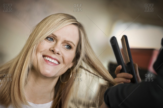 Smiling young woman getting her long hair straightened with a hair iron