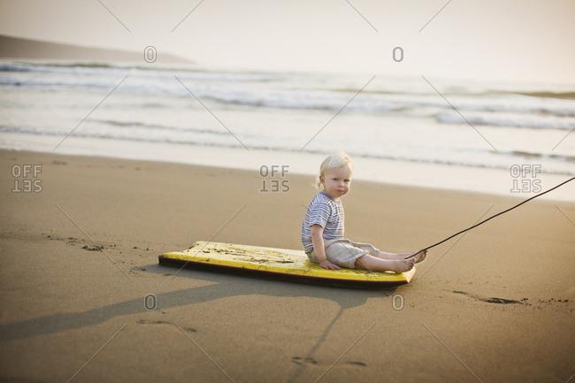 Little boy being pulled along beach on a boogie board