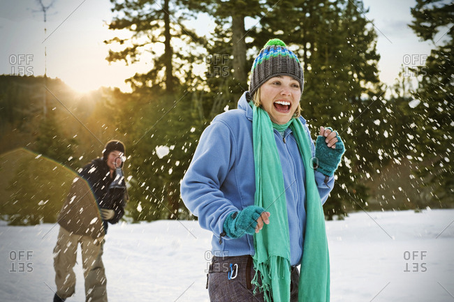 Laughing young woman wearing a knitted hat getting hit by a snowball from behind while out in the snow with friends