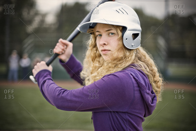 Portrait of a confident young woman wearing a helmet and holding a baseball bat