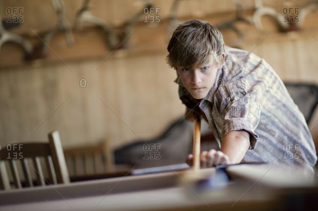 Focused teenage boy playing pool