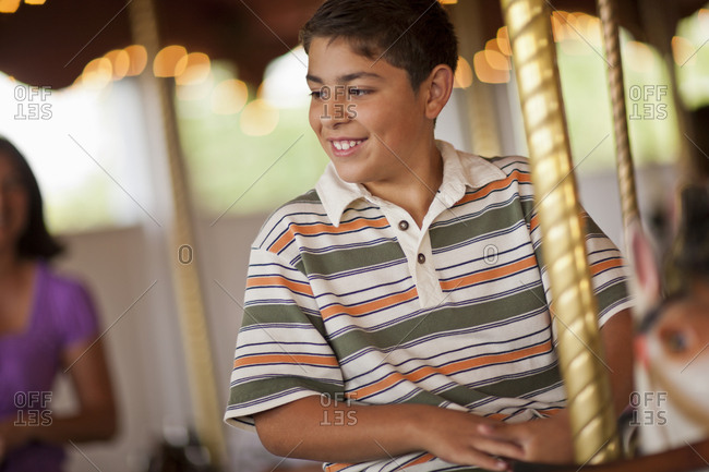 Smiling young boy riding a carousel at an amusement park
