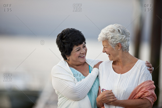 Two happy mature women have fun together as they chat and walk along a jetty