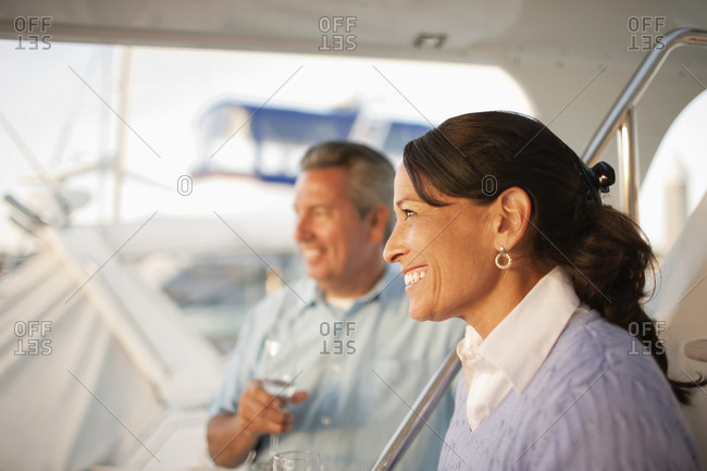 Middle aged couple look out to sea while standing on a boat deck.