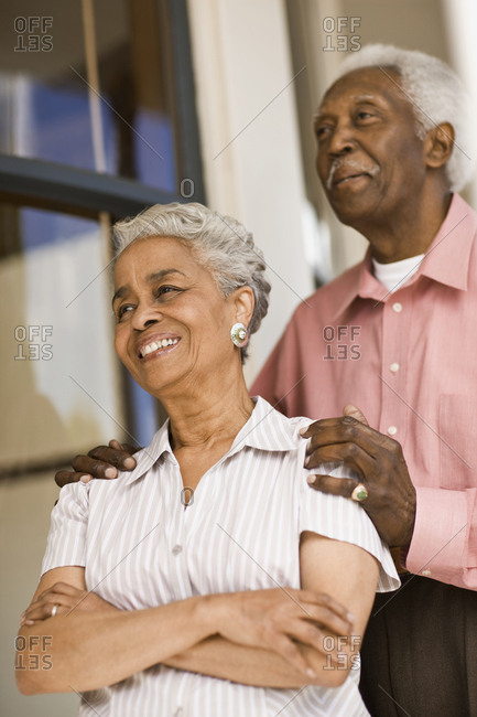 Senior African American couple smile whilst standing outside a house.