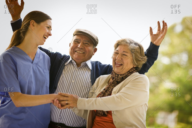 Female nurse and senior couple laugh and talk as a senior man throws up his arms happily
