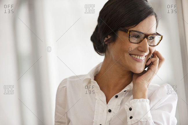Businesswoman wearing eyeglasses smiles as she takes a call on a cell phone