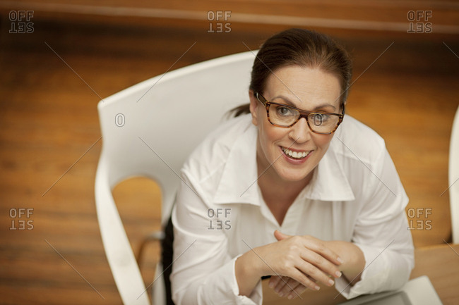 Businesswoman sitting at a desk with her hands clasped looks up and smiles as she poses for a portrait