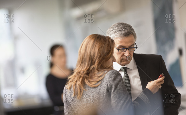 Businesswoman and man looking at something on a cell phone