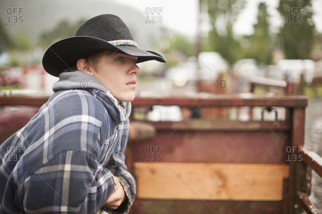 Teen wearing cowboy hat, looking over fence into rodeo arena.