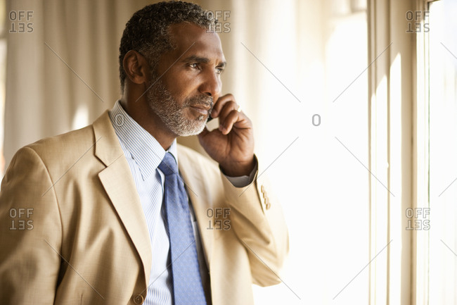 Angry-looking businessman talking on cell phone.