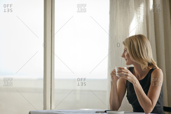 Mid adult woman enjoying a cup of tea at a table