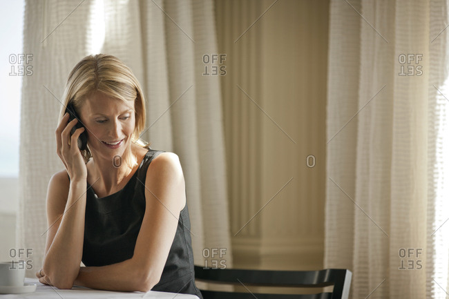 Smiling woman talking on a cell phone while sitting at a table