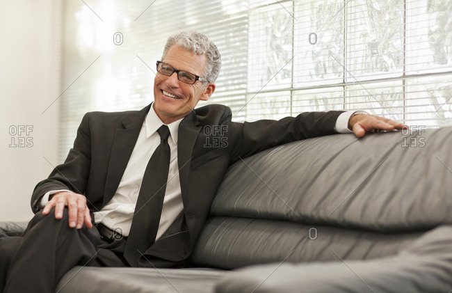 Smiling mature man sitting on a sofa