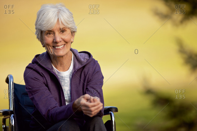 Smiling senior woman sitting in a wheel chair
