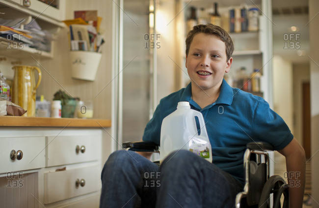 Teenage boy sitting in a wheelchair with a plastic bottle of milk