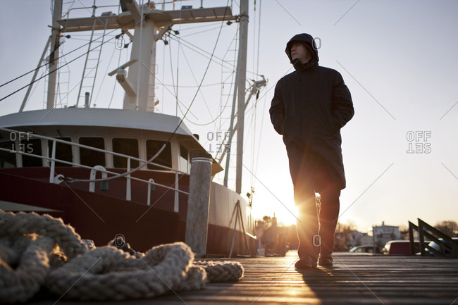 Mid adult man walking along a wharf next to a moored trawler with his hands in his pockets