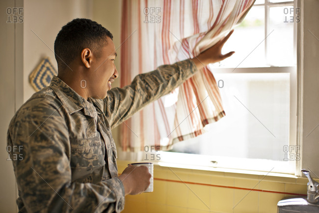 Smiling young adult soldier holding a mug while looking out the window of his home