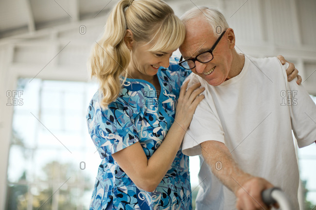 Happy young nurse comforting a senior man