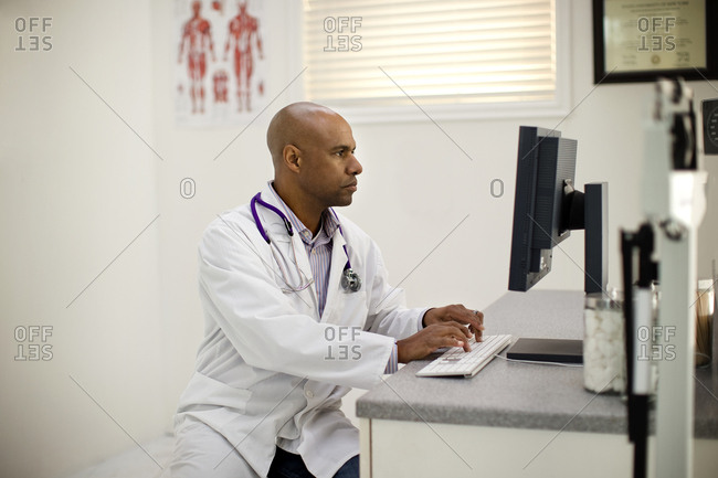 Mid adult doctor sitting at a desk working on a computer