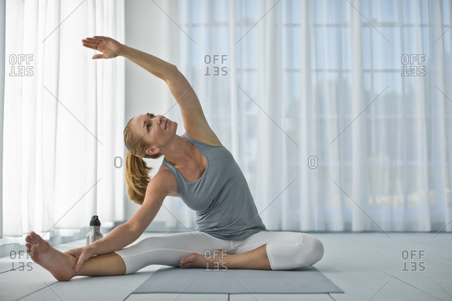Happy mid adult woman stretching her arms and legs while practicing yoga