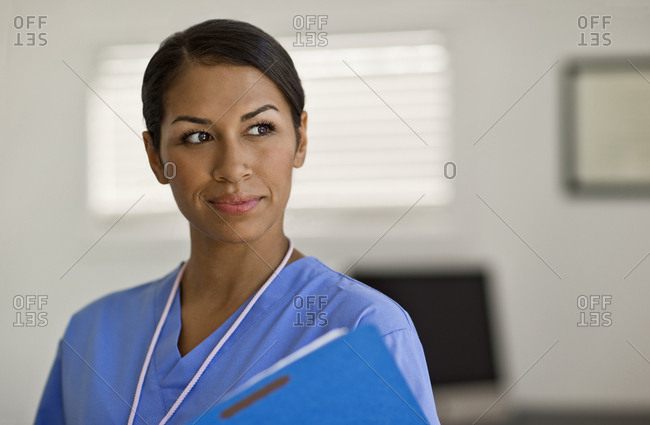 Pretty young nurse looking thoughtful as she examines a patients note