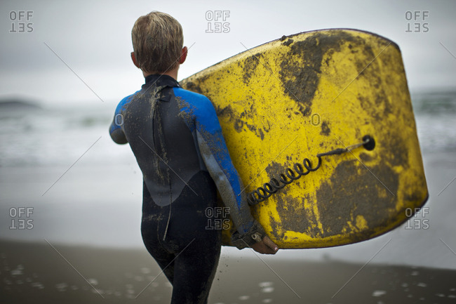 Young boy in a wetsuit carrying a surfboard