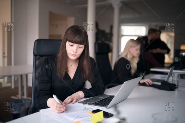 Businesswoman working on computer as colleagues discuss in background