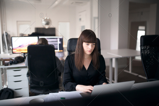 Businesswoman working on computer as colleague works in background