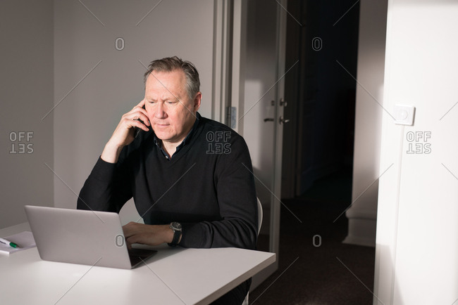 Older businessman talking on phone and working at computer
